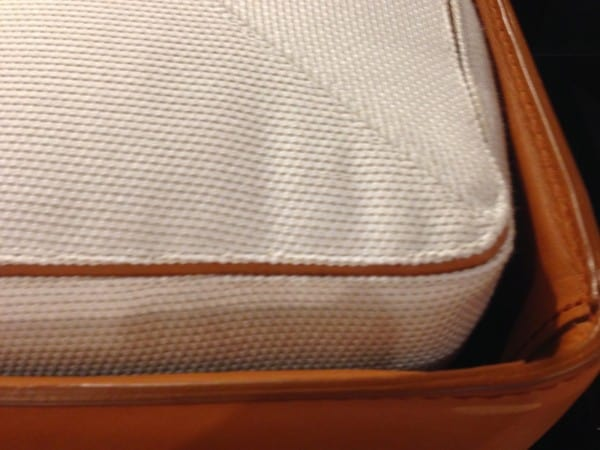 Cushion seams are outlined in fine leather trim