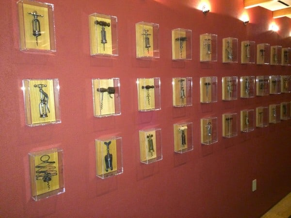A wall in the private Dining room at Boulud Sud: Antique corkscrews framed in Plexiglass