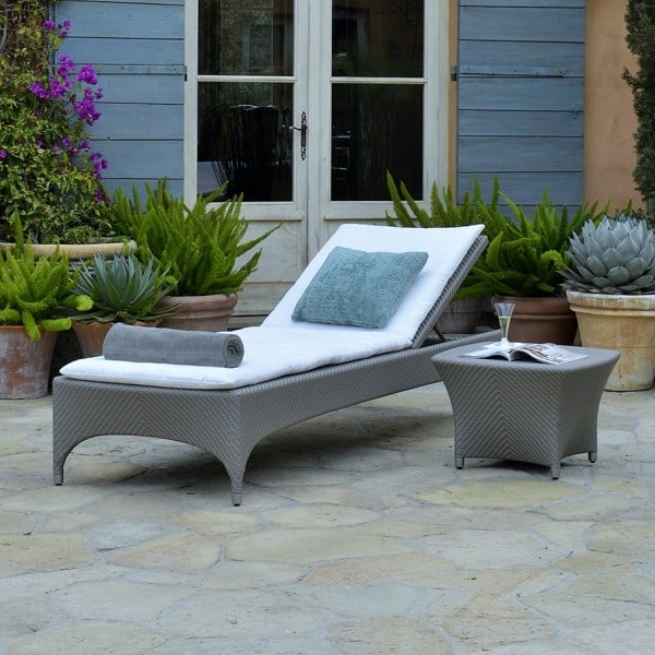 Palladium finish Amari Chaise Lounge and table on the patio