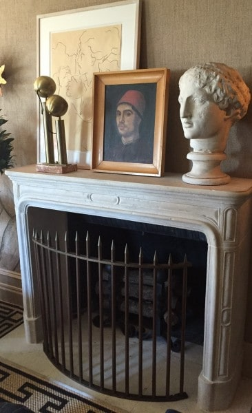 large antiquity bust, renaissance style painting, found objects on stands and an oversize framed pencil drawing.