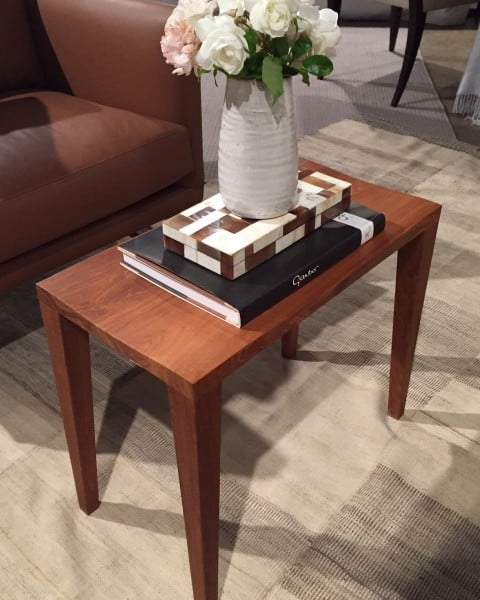 A book and a bone box are elevate a simple white vase.