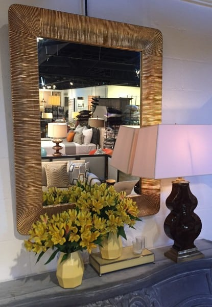 mirror is accented by a lamp and a collection of like colored accessories and flowers